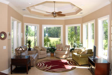 Walls of windows in the sunroom bring the outdoors inside.