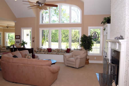 An abundance of natural light floods the main living areas of the home.  Here the living room's generous windows provide expansive views to the outside.