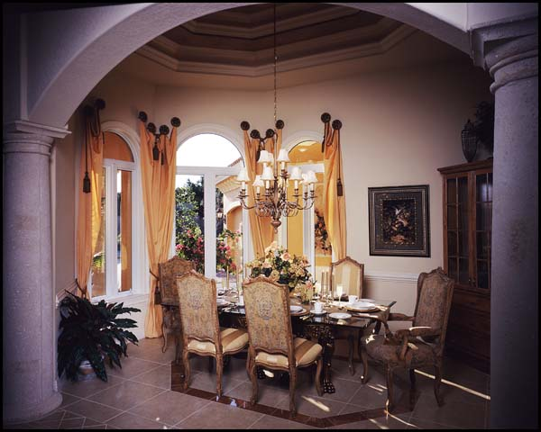 The dining room embellished with arches and columns is brightened by a trio of arch-topped windows.