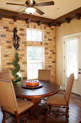 The breakfast area is brightened by plenty of natural light and access a rear covered patio.